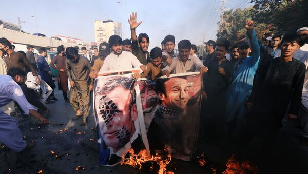 People chant slogans as they set fire to a banner with an image of French President Emmanuel Macron during a protest against cartoon publications of Prophet Mohammad in France and French President Emmanuel Macron's comments, in Peshawar, Pakistan 27 October 2020. - Sputnik International