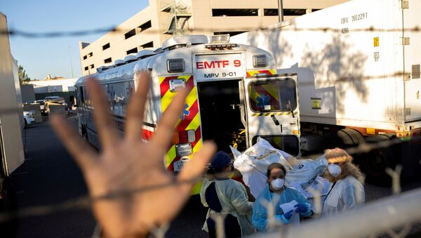 An El Paso County Sheriff's Officer tries to block photographs from being taken as bodies are moved to refrigerated trailers, deployed during a surge of coronavirus disease (COVID-19) deaths, outside the County of El Paso Medical Examiners Office in El Paso, Texas, 16 November 2020 - Sputnik International