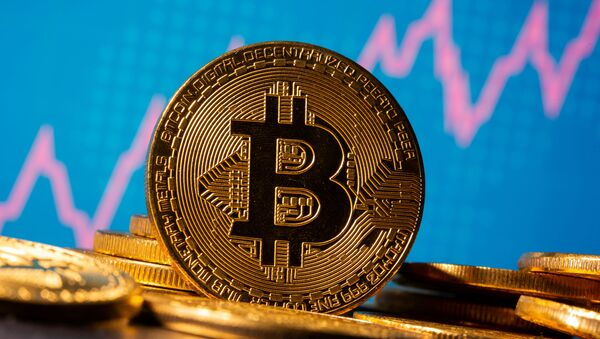 A representation of virtual currency Bitcoin is seen in front of a share graph in this illustration taken 19 November 2020. - Sputnik International