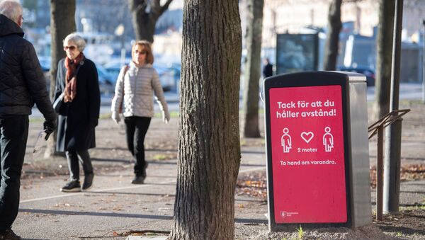 People strollIing in the cold but sunny weather pass a sign asking to maintain social distancing, amid the continuous spread of the coronavirus disease (COVID-19) pandemic, in Stockholm, Sweden, November 20, 2020 - Sputnik International