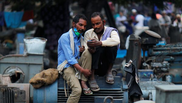 Men wearing protective face masks on their chins, amid the coronavirus disease (COVID-19) outbreak, watch a video on a mobile phone as they sit at a second-hand motor parts market in the old quarters of Delhi, India, November 16, 2020 - Sputnik International