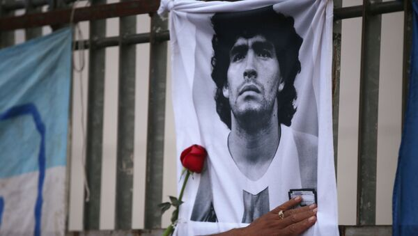 A rose is placed next to a banner of Argentine soccer great Diego Maradona as fans gather to mourn his death, at the Obelisk of Buenos Aires, Argentina November 25, 2020 - Sputnik International
