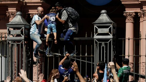 Men help a child to climb on the fence of the Casa Rosada presidential palace as people gather to mourn the death of soccer legend Diego Armando Maradona, in Buenos Aires, Argentina, 26 November 2020. - Sputnik International