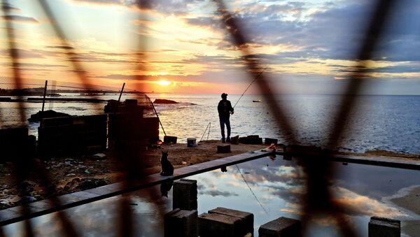 A fisherman is pictured along the promenade in Libya's capital Tripoli on November 25, 2020.  - Sputnik International
