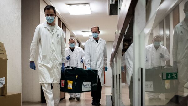 In this handout photo released by Hungarian Foreign Ministry, laboratory assistants carry a bag with Russia's coronavirus vaccine Gam-COVID-Vac, trade-named Sputnik V inside, in Budapest, Hungary - Sputnik International