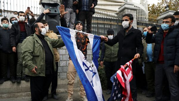 Protesters burn the U.S. and Israeli flags during a demonstration against the the killing of Mohsen Fakhrizadeh, Iran's top nuclear scientist, in Tehran, Iran, November 28, 2020.  - Sputnik International