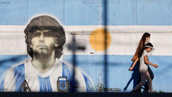 People walk past graffiti featuring soccer legend Diego Armando Maradona in Buenos Aires, Argentina, 27 November 2020 - Sputnik International