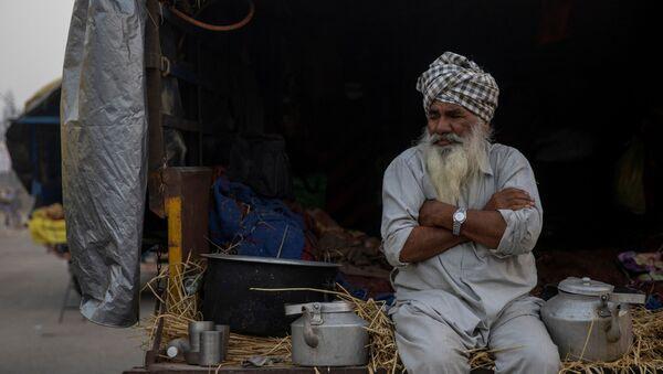 A farmer sits in a tractor trolley during a protest against the newly passed farm bills at Singhu border near Delhi, India, November 30, 2020. - Sputnik International