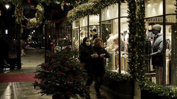 Women wearing face masks walk past a Christmas tree and lights in Burlington Arcade, where all non-essential shops are temporarily closed during England's second coronavirus lockdown, in London, Wednesday, Nov. 25, 2020 - Sputnik International