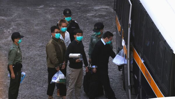 Pro-democracy activists Ivan Lam and Joshua Wong walk to a prison van to head to court, after pleading guilty to charges of organising and inciting an unauthorised assembly near the police headquarters during last year's anti-government protests, in Hong Kong, China December 2, 2020 - Sputnik International
