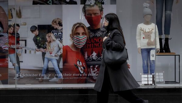 A woman wearing a face shield walks past the front window of the Primark clothing store on Oxford Street during England's second coronavirus lockdown, in London, Monday, Nov. 23, 2020 - Sputnik International