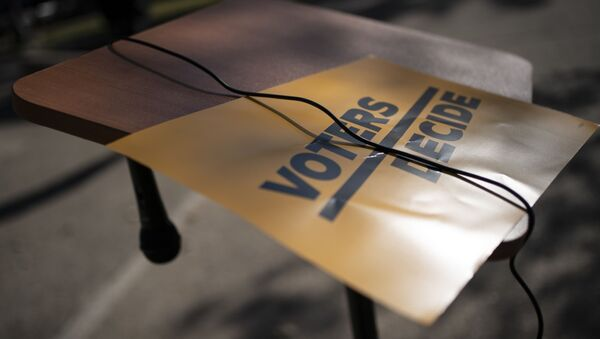 A sign that reads Voters Decide is placed next to a hanging microphone as people gather at the Civic Center Park while waiting for the results of election, Wednesday, Nov. 4, 2020, in Kenosha, Wis. - Sputnik International
