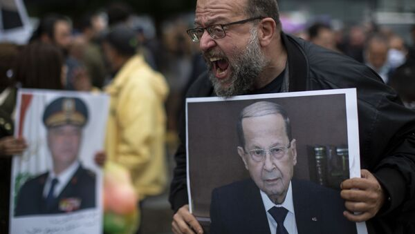 An anti-government protester holds a picture of Lebanese President Michel Aoun as he shouts slogans during a protest, in Beirut's Ashrafieh district, Lebanon, Thursday, Nov. 26, 2020. - Sputnik International