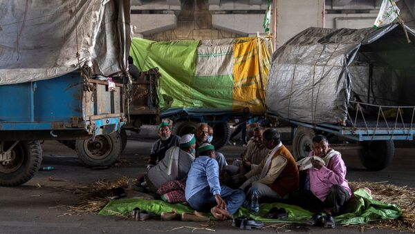 Farmers rest near their parked tractor trolleys at the site of a protest against the newly passed farm bills at the Delhi-Uttar Pradesh border in Ghaziabad, India - Sputnik International