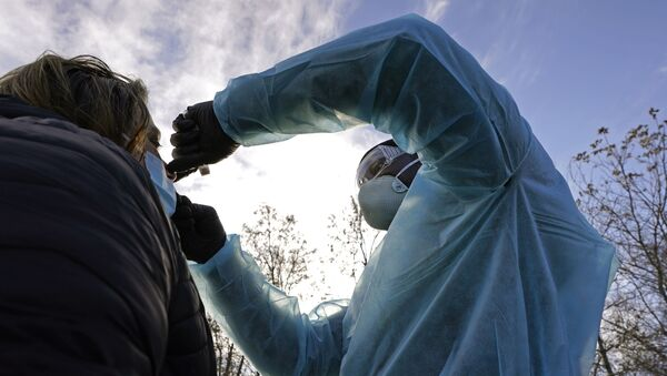 LPN Yeonis Jean Jacques administers a COVID-19 test to a woman, Thursday, Dec. 3, 2020, in Lawrence, Mass. - Sputnik International