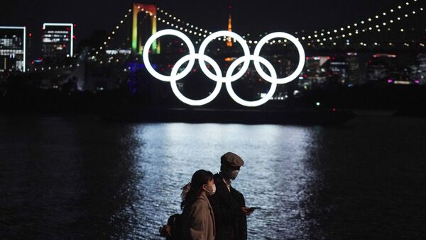 A man and a woman walk past near the Olympic rings floating in the water in the Odaiba section Tuesday, Dec. 1, 2020, in Tokyo. The Olympic Symbol was reinstalled after it was taken down for maintenance ahead of the postponed Tokyo 2020 Olympics. - Sputnik International