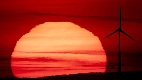 The sun rises behind a wind turbine in Frankfurt, Germany, early Tuesday, Sept. 15, 2020. - Sputnik International
