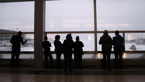 Stranded travelers and airport workers watch front loaders clear snow from the apron around Gates C and D at Terminal B at LaGuardia Airport, Thursday, Jan. 4, 2018, in New York. - Sputnik International