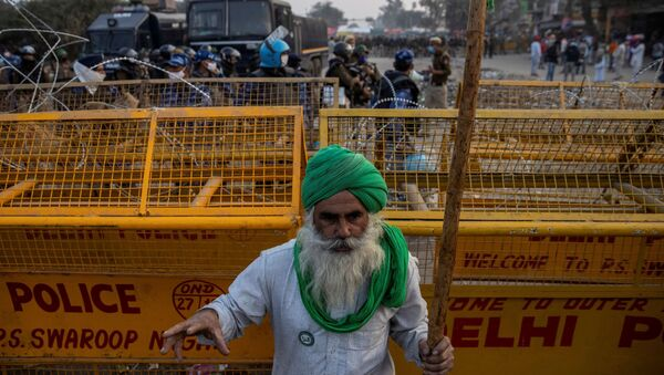 A farmer stands in front of police barricades during a protest against the newly passed farm bills at Singhu border near Delhi, India, December 3, 2020 - Sputnik International