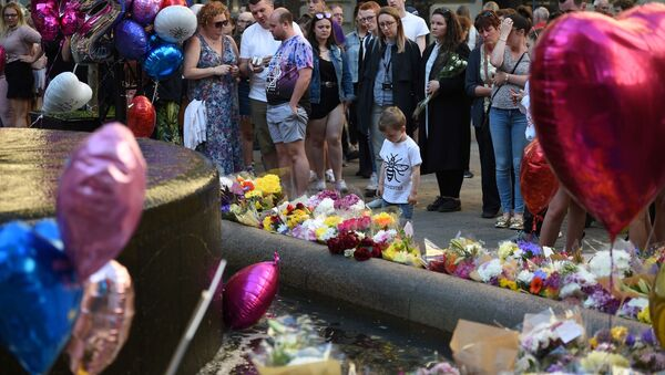 People pay their respects as they look at flowers and balloons left in central Manchester on May 22, 2018, the one year anniversary of the deadly attack at Manchester Arena.  - Sputnik International