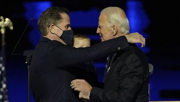 US President-elect Joe Biden (R) embraces his son Hunter Biden (L) on stage after delivering remarks in Wilmington, Delaware, on 7 November 2020.  - Sputnik International