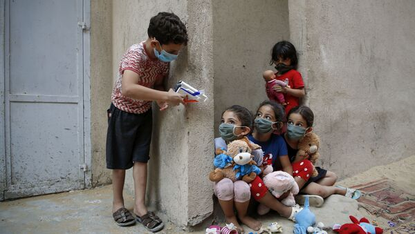 Palestinian children, mask-clad due to the Covid-19 coronavirus pandemic, play outside their house in Gaza City on 8 September - Sputnik International