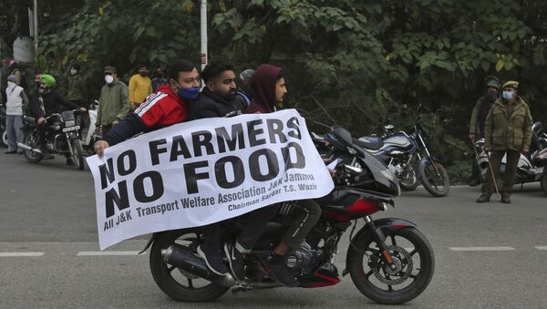 Protestors hold a placard and join others as they block the Jammu-Pathankot higway during a nationwide shutdown called by thousands of Indian farmers protesting new agriculture laws in Jammu India, Tuesday, Dec. 8, 2020 - Sputnik International