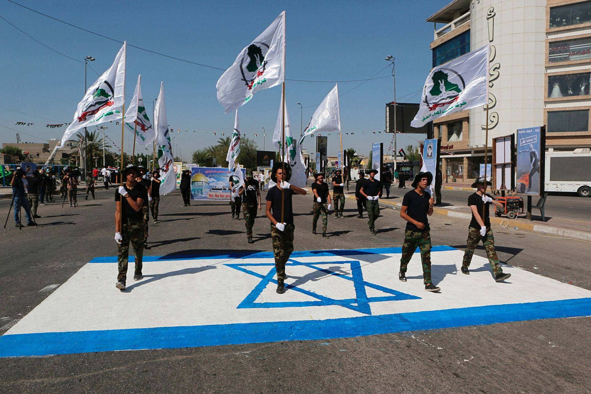 Iraq's Iranian-supported Popular Mobilization Forces militiamen marching over an Israeli flag drawn on the street in Baghdad, May 2019. - Sputnik International, 1920, 07.09.2021