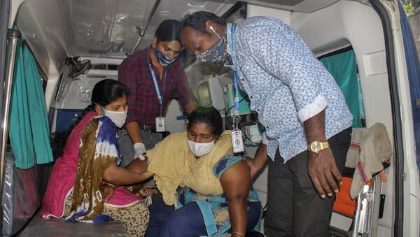 A patient is assisted by others to get down from an ambulance at the district government hospital in Eluru, Andhra Pradesh state, India, Tuesday, Dec.8, 2020 - Sputnik International