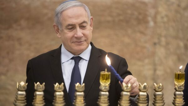 Israeli Prime Minister Benjamin Netanyahu, lights a Hanukkah candle at the Western Wall, the holiest site where Jews can pray in Jerusalem's old city, Sunday, Dec. 22, 2019 - Sputnik International
