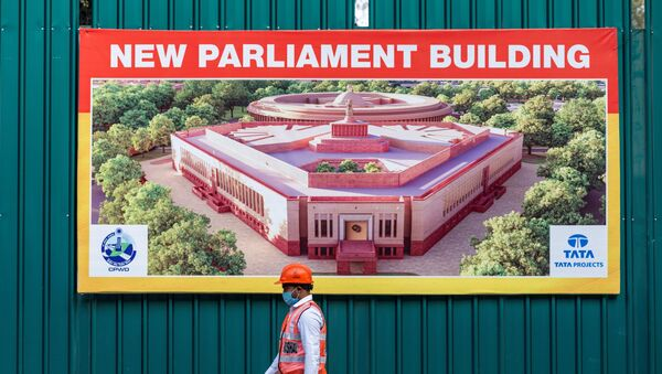A worker walks past a banner at the boundary of the new Indian Parliament house construction site in New Delhi on December 10, 2020.  - Sputnik International