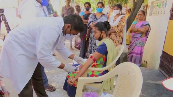 Healthcare personnel takes a blood sample from a patient during an examination, after hundreds of people were hospitalised due to an unknown illness in the southern state of Andhra Pradesh, in this still frame taken from video dated December 9, 2020 - Sputnik International