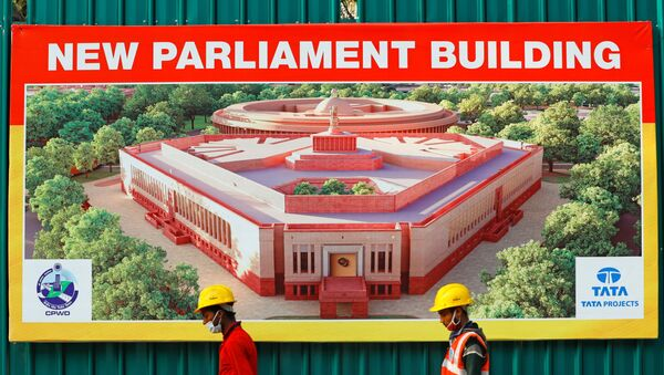 Construction workers walk past a hoarding featuring India's new parliament building outside its construction site in New Delhi, India, December 10, 2020. - Sputnik International