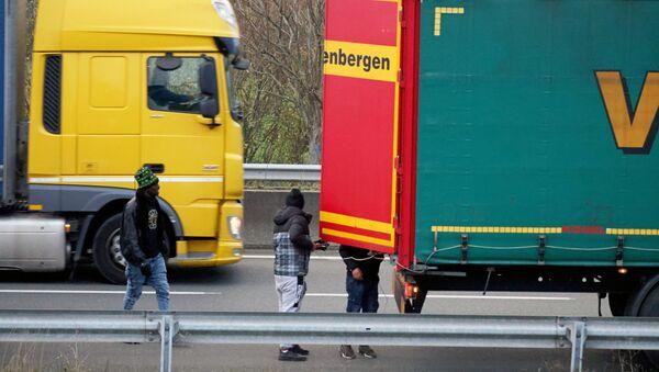 Migrants try to hide inside trucks waiting on the road in Calais - Sputnik International