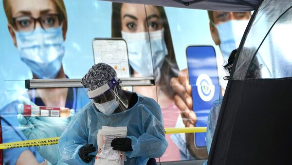 A health care employee works at a walk-up COVID-19 testing site, Wednesday, Nov. 18, 2020, in Miami - Sputnik International