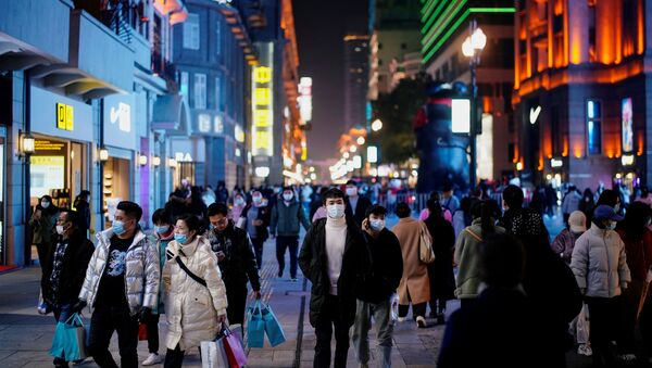 People wearing face masks are seen at a main shopping area almost a year after the global outbreak of the coronavirus disease (COVID-19) in Wuhan, Hubei province, China December 7, 2020. Picture taken December 7, 2020 - Sputnik International