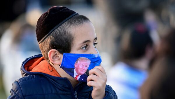 A child wears a protective face mask depicting U.S. President Trump at the 2020 annual National Chanukah Menorah Lighting near the White House in Washington - Sputnik International