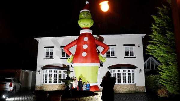 People pose in front of a giant inflatable character The Grinch outside a house, amid the outbreak of the coronavirus disease (COVID-19) in Hartlepool, Britan November 29, 2020. - Sputnik International