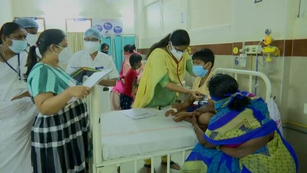A doctor examines a young patient lying in a hospital bed at an Eluru hospital, after hundreds of people were hospitalised due to an unknown illness in the southern state of Andhra Pradesh, in this still frame taken from video dated December 9, 2020 - Sputnik International