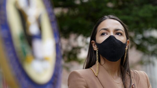 Rep. Alexandria Ocasio-Cortez, D-NY, wears a protective mask as she waits to speak during a news conference outside the USPS Jamaica station, Tuesday, Aug. 18, 2020, in the Queens borough of New York. The Postal Service said it has stopped removing mailboxes and mail-sorting machines amid an outcry from lawmakers, as President Donald Trump denied he was slowing service. Democrats and some Republicans say actions by a Trump ally and a major Republican donor, new Postmaster General Louis DeJoy, have endangered millions of Americans who rely on the Postal Service for prescription drugs and other needs.  - Sputnik International