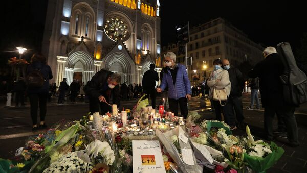 People light candles outside Notre-Dame de l'Assomption Basilica in Nice on October 31, 2020, to pay tribute to the victims two days after a knife attacker killed three people, cutting the throat of two, inside the church of the French Riviera city, and police arrest a young Tunisian migrant from Sfax who arrived in Europe only last month, according to French prosecutors.  - Sputnik International