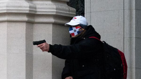 A man wearing a protective mask points his guns outside the Cathedral Church of St. John the Divine in the Manhattan borough of New York City, New York, U.S., December 13, 2020. - Sputnik International