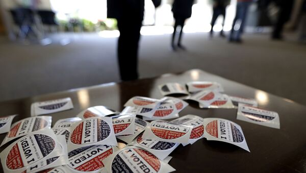 In this March 17, 2020, file photo I Voted stickers sit on the table for voters at Trinity Lutheran Church in Evanston, Ill. The U.S. intelligence community has warned over and over that foreign adversaries can and will interfere in the 2020 presidential election.  Just six weeks before the first ballots are cast, the threat has never been higher, and there are new signs that the nation's electoral system is already under attack. - Sputnik International