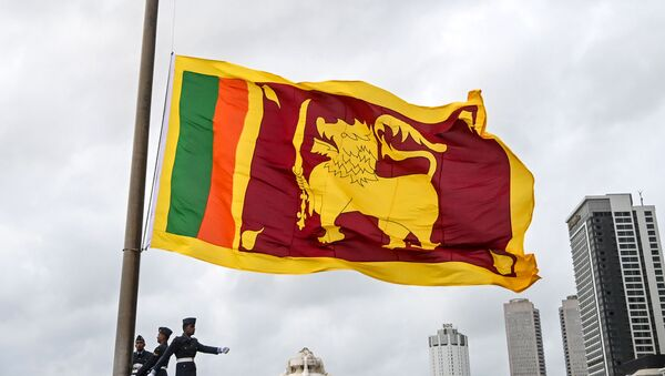 Soldiers stand at attention as the national flag is lowered as part of a daily ceremony at the Galle Face Green promenade in Colombo on May 17, 2020. - Sputnik International