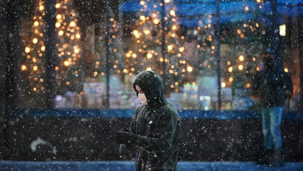 A person wearing a protective face mask walks as snow begins to fall in Times Square during a Nor'easter, during the coronavirus disease (COVID-19) pandemic in the Manhattan borough of New York City, New York, U.S., December 16, 2020 - Sputnik International