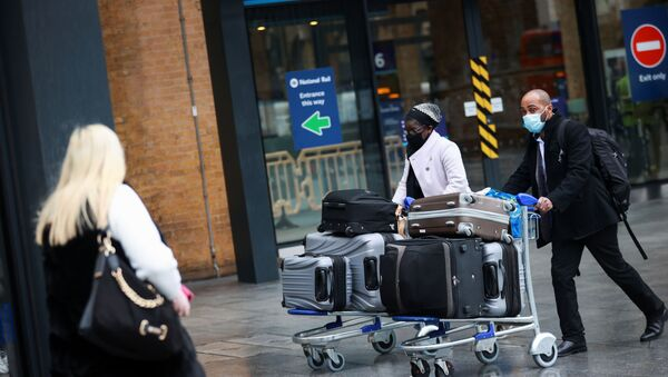 Travellers walk with their luggage at King's Cross station, as EU countries impose a travel ban from the UK following the coronavirus disease (COVID-19) outbreak, in London, Britain, December 21, 2020. - Sputnik International