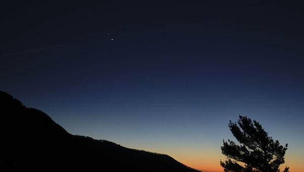 """Saturn, top, and Jupiter, below, are seen after sunset from Shenandoah National Park, Sunday, Dec. 13, 2020, in Luray, Virginia. The two planets are drawing closer to each other in the sky as they head towards a """"great conjunction"""" on December 21, where the two giant planets will appear a tenth of a degree apart. - Sputnik International"""