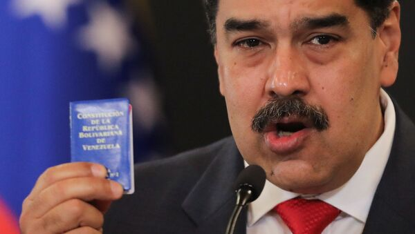 Venezuelan President Nicolas Maduro holds Venezuela's constitution as he speaks during a press conference following the ruling Socialist Party's victory in legislative elections that were boycotted by the opposition in Caracas, Venezuela December 8, 2020.  - Sputnik International