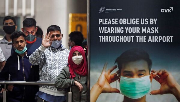 People wearing protective face masks wait for passengers to arrive at Chhatrapati Shivaji Maharaj International Airport after India cancelled all flights from the UK over fears of a new strain of the coronavirus disease (COVID-19), in Mumbai, India, December 22, 2020.  - Sputnik International