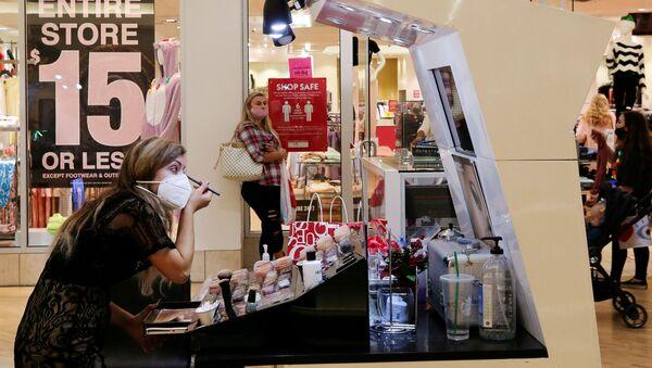 An employee wearing a protective mask applies makeup at Coastal Grand Mall on Black Friday, as the coronavirus disease (COVID-19) pandemic continues, in Myrtle Beach, South Carolina, U.S., November 27, 2020 - Sputnik International
